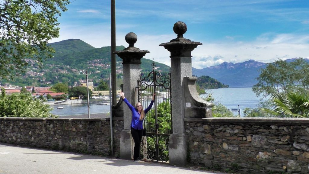 Vista from the Villa Taranto Botanical Gardens, Lake Maggiore, Italy - Dina arms outstretched in from of an wrought iron gate with lake in background